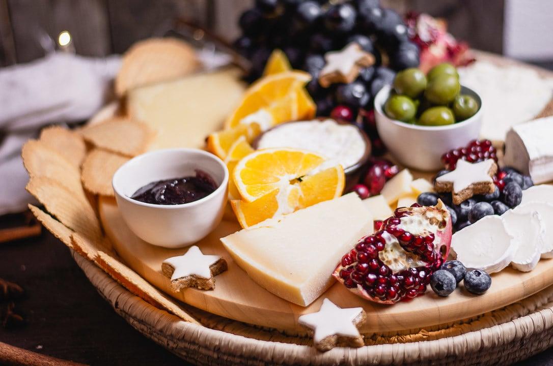 Pecorino Käse auf der Käseplatte neben rotem Feigensenf, Ziegenkäse und Granatapfel