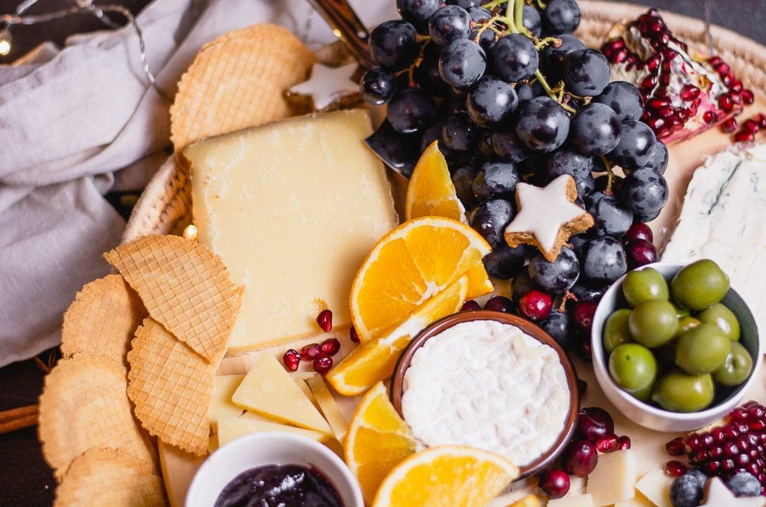 Orangenspalten, Weintrauben, Granatapfel, Oliven und Zimtsterne liegen als Dekoration auf der Käseplatte