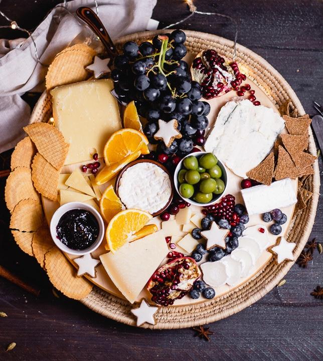 Mit Crackern dekoriert ist die Käseplatte fertig. Damit die Cracker nicht verloren gehen steht das runde Brett der Käseplatte in einem runden Basttablett