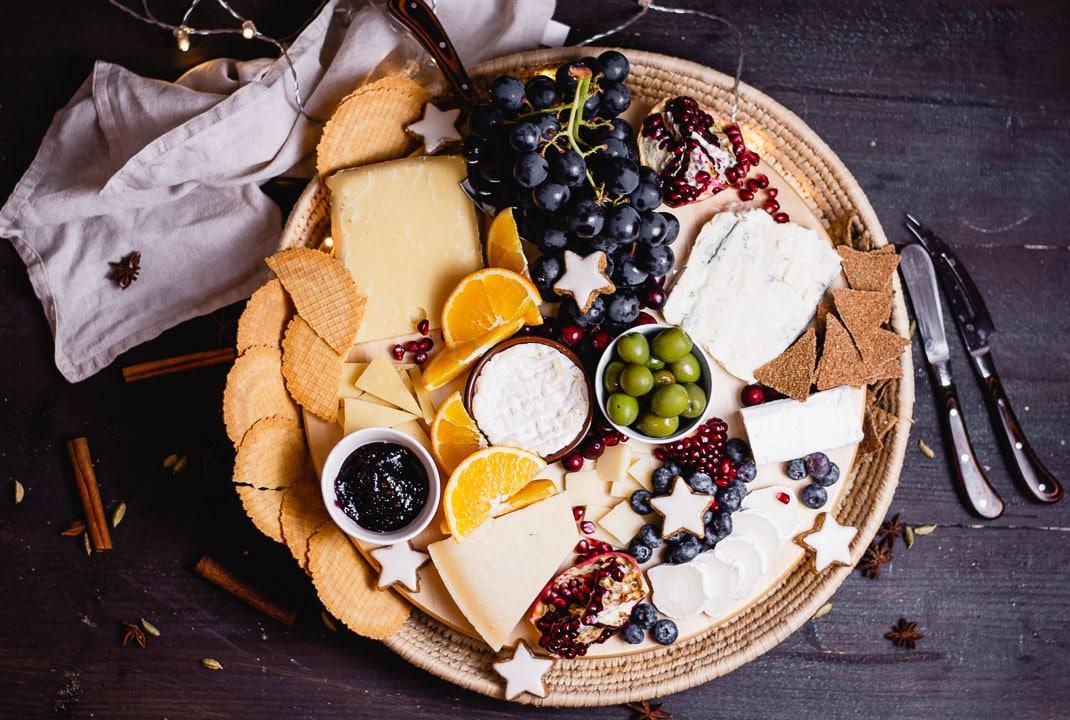 Käseplatte mit Weintrauben, Granatapfel, Oliven, Crackern und Zimststernene von oben fotografiert