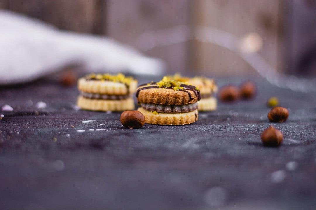 Drei Mozarttaler und Nüsse auf einem shwarzen Tisch