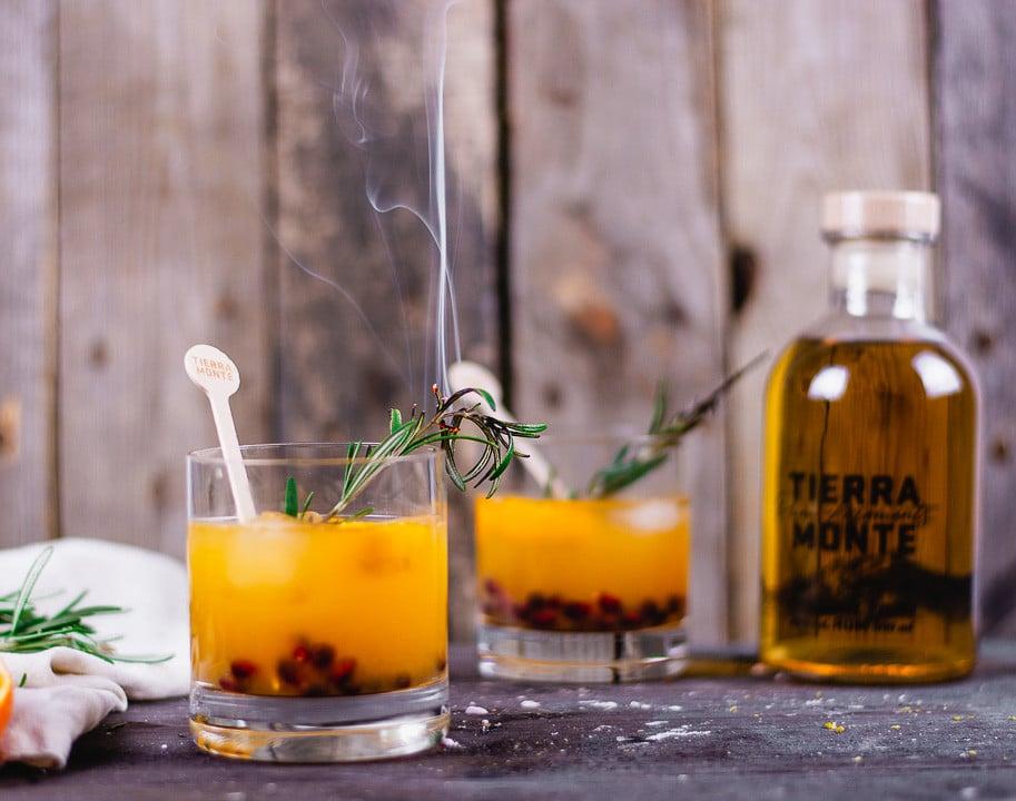 Zwei Rum Cocktails mit einem rauchenden Rosmarin Zweig