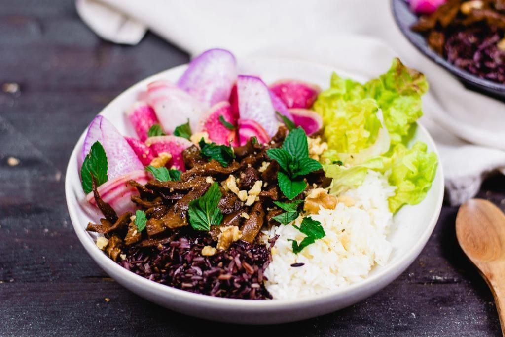 Ein Teller mit Radieschen, Pilzen, Salat und zwei unterschiedlichen Reissorten