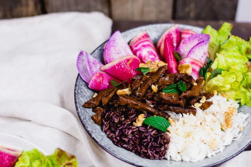 Ein Teller mit winterliche Bowl. Man erkennt Reis, Radieschen, Salat und Pilze