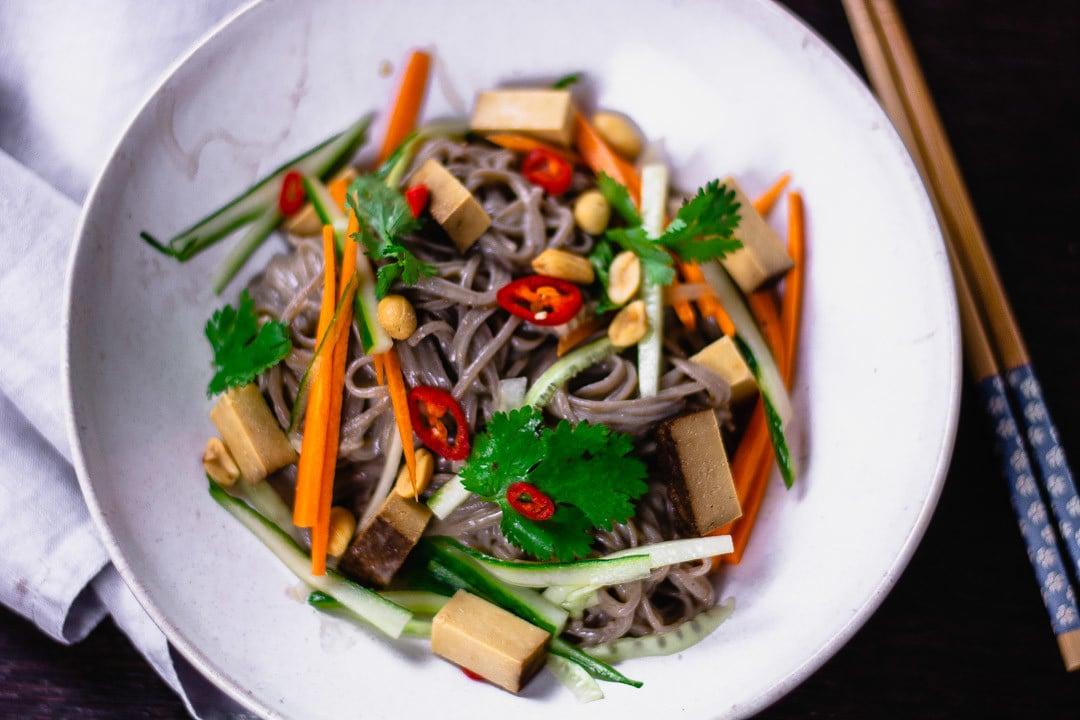 Ein Teller veganer Nudelsalat in der Nahaufnahme. Man erkennt Erdnüsse, Nudeln, Tofu und Chili
