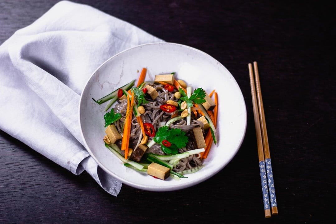 Ein Teller mit Nudeln, Tofu, Erdnüssen und vielen mehr für Veganer