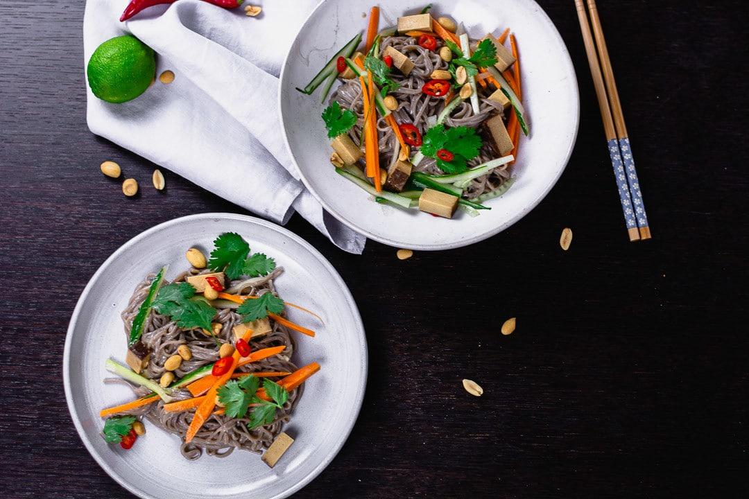 Zwei Teller mit Nudelsalat vegan. Daneben liegen Stäbchen und Erdnüsse