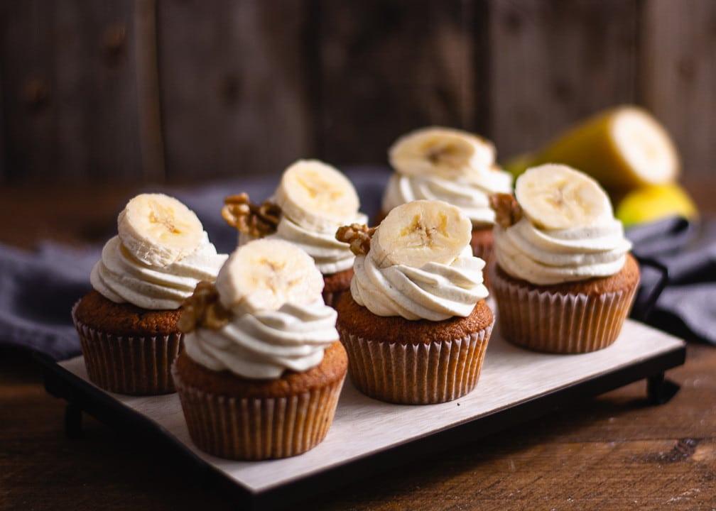 Sechs Bananen Cupcakes auf einem Holzteller