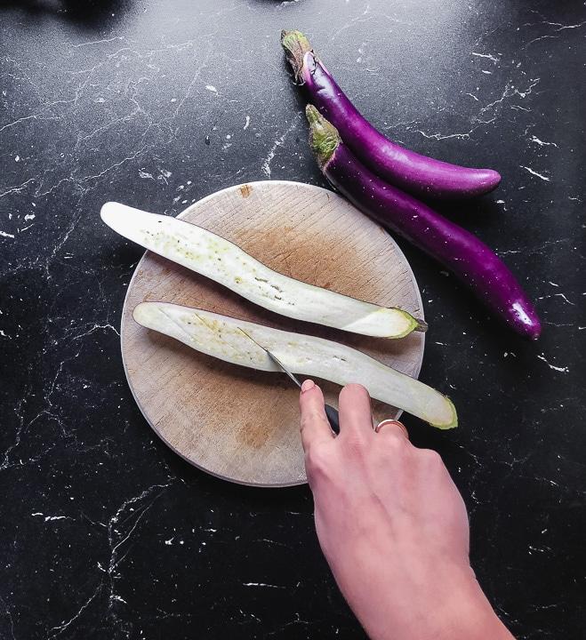 Eine Aubergine wird halbiert und eingeschnitten