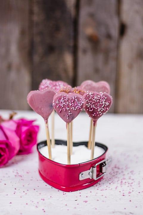 Viele Herz Cake Pops in einer Herzform auf einem weißen Tisch