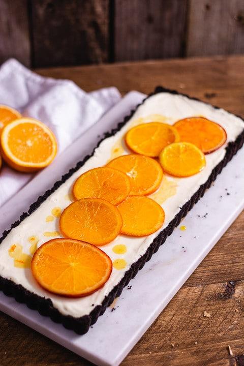 Orangentarte von der Seite auf einem Mamorbrett