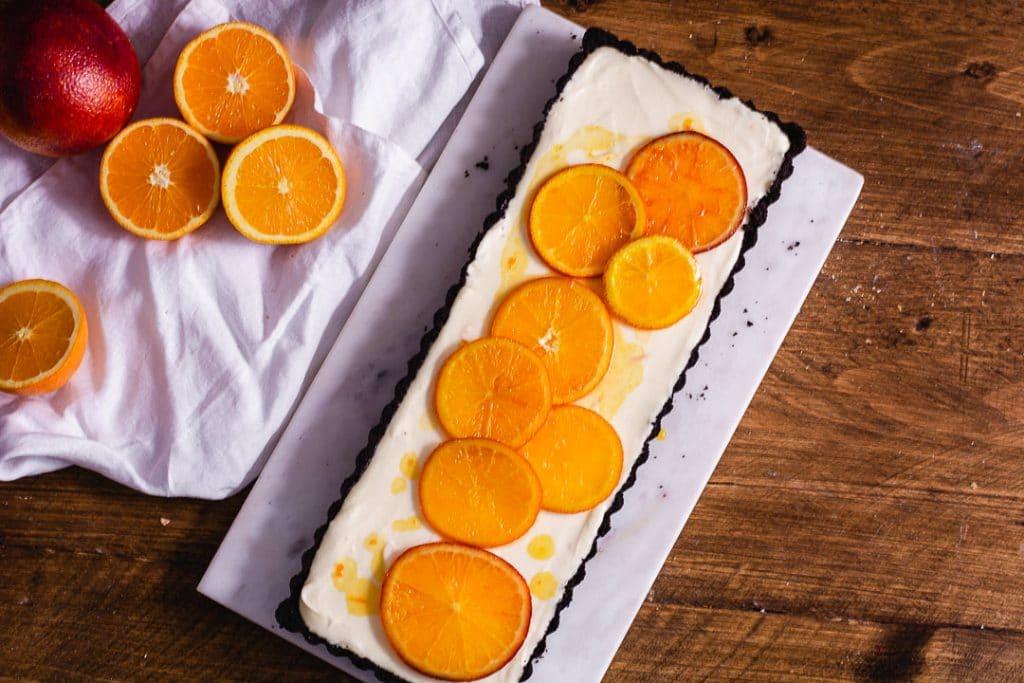 Orangentarte als Topshot. Daneben liegen Orangen als Deko