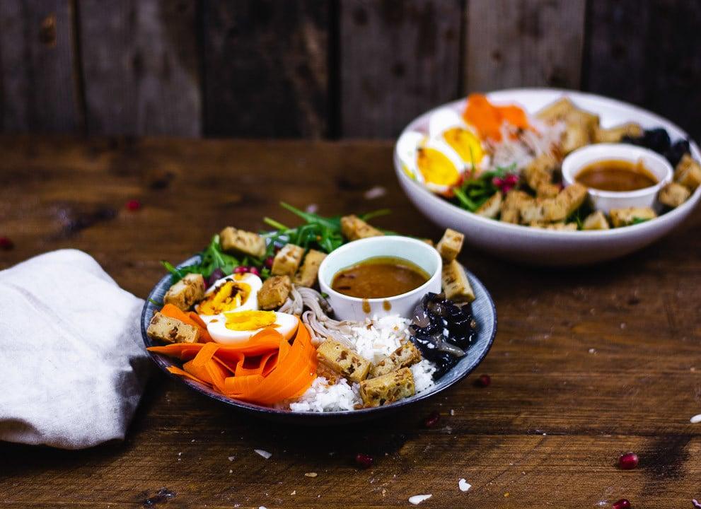Zwei Bowl Teller auf einem Holtisch mit Erdnusssauce