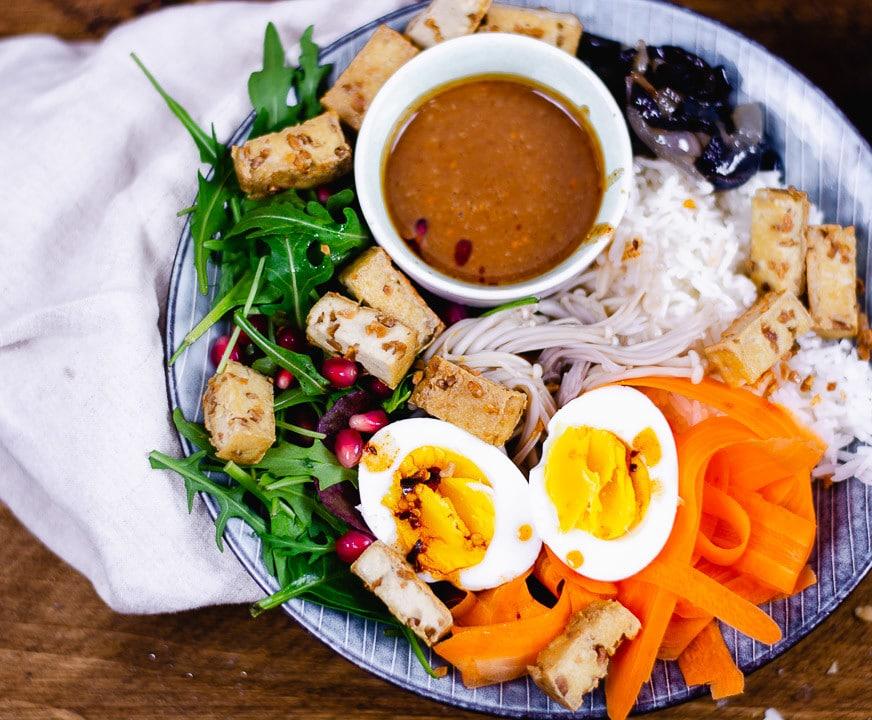 Ein Bowl Rezept auf einem blauen Teller angerichtet. Man sieht Ei, Karottenstreifen, Tofu, Sauce und Reis