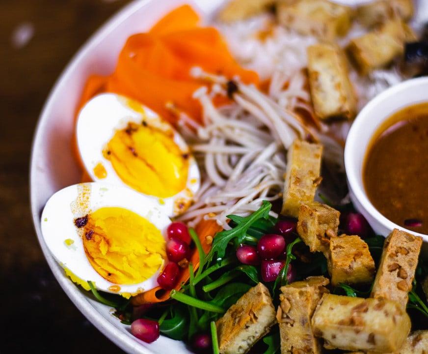 Das Bowl Rezept in der Nahaufnahme. Man sieht zwei Eier, Tofu, Pilze und eine Erdnusssauce