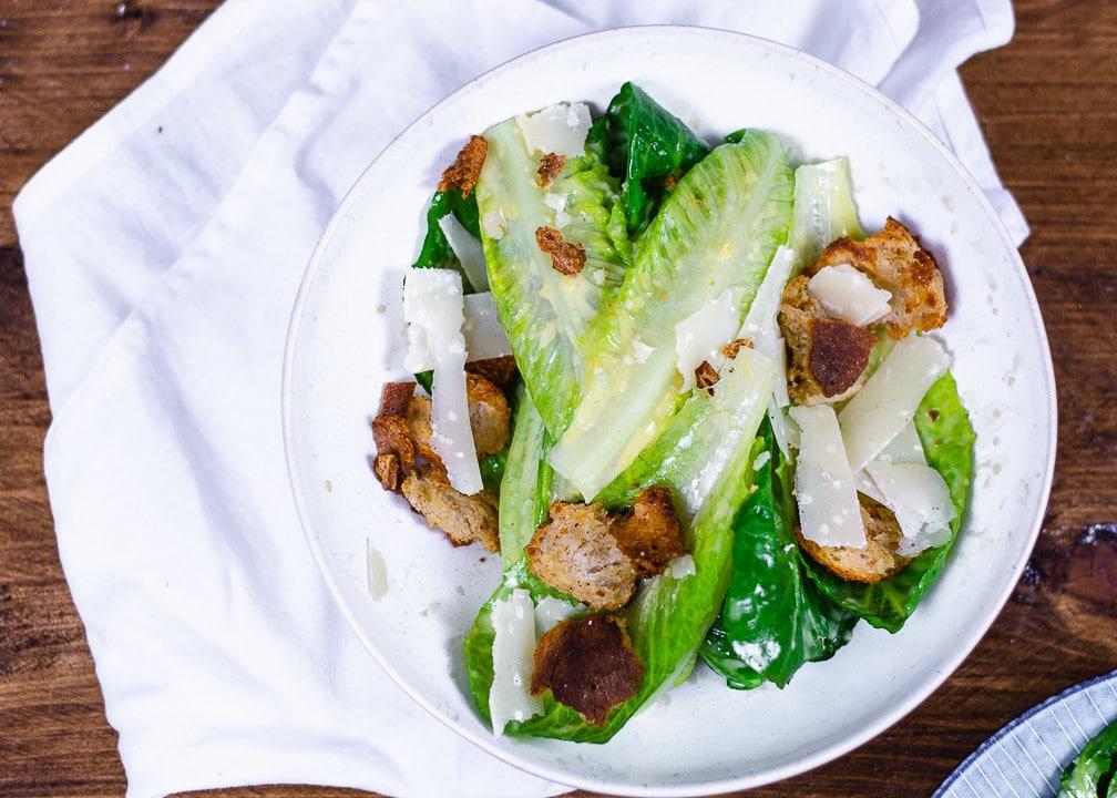 Ein Caesar Salad Topshot. Man erkennt Croutons und Parmesan im Salat
