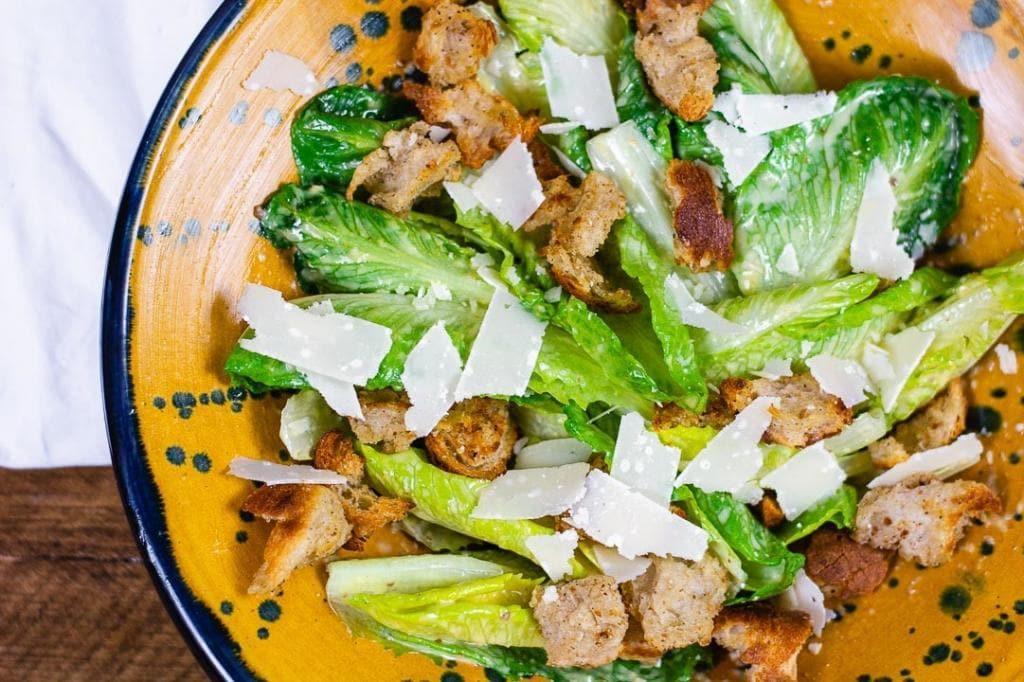 Ein Caesar Salad in einer gelber Schüssel