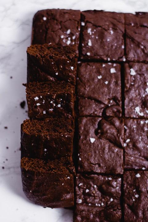 Zwölf Stücke Schoko Brownies, wobie vier davon aufgestellt sind. Man sieht wie schokoladig die Brownies sind