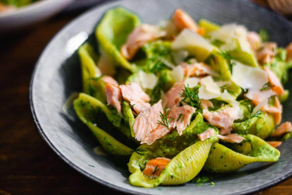 Man erkennt grüne Nudeln, Lachs und Garnitur auf einem Teller