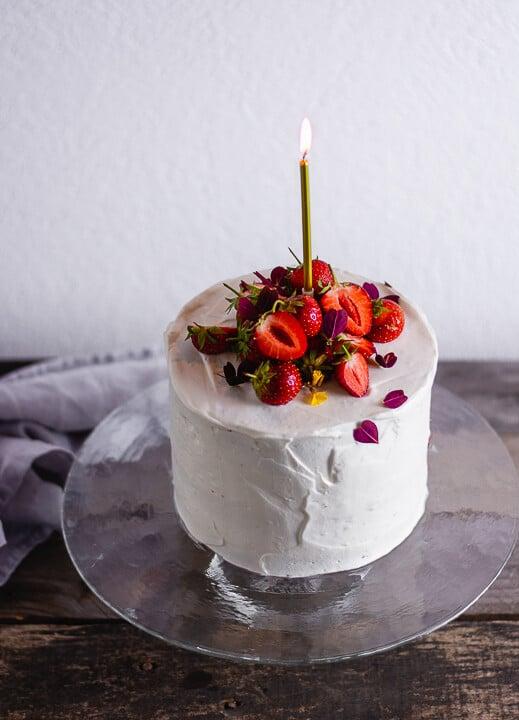 Ein Kuchen in weiß mit Erdbeeren auf dem Kuchen und einer goldenen Kerze die brennt