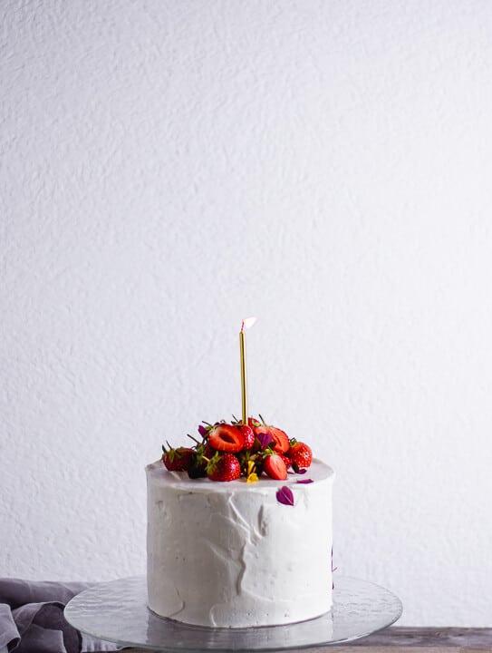 Eine Kerze wird auf dem Geburtstagskuchen ausgepustet