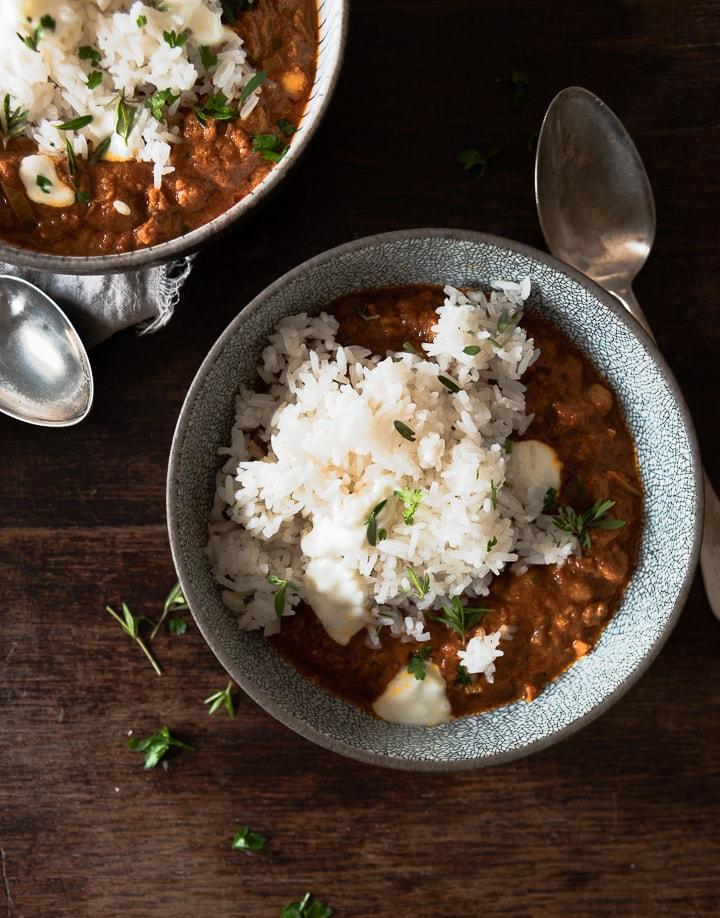 Das fertig Kichererbsen Curry mit Reis in einem tiefen Teller mit Löffel.
