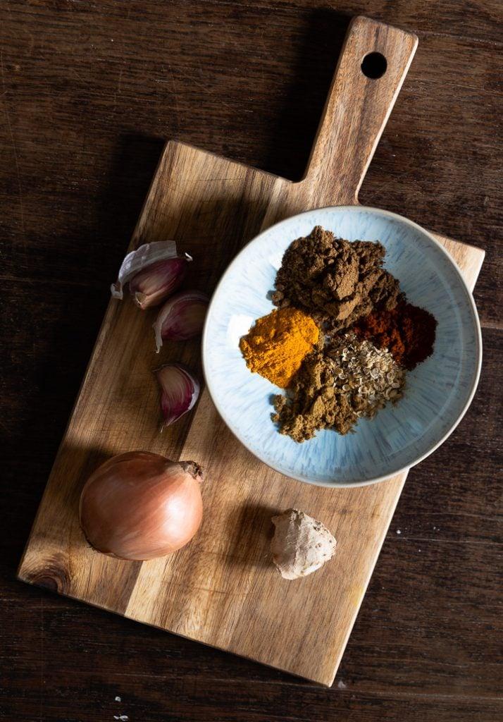 Die Zutaten für das Kichererbsen Curry liegen auf einem Brettchen.