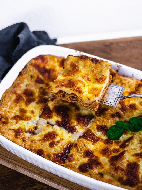 Ein Stück Lasagne wird aus einer Lasagne hochgehoben