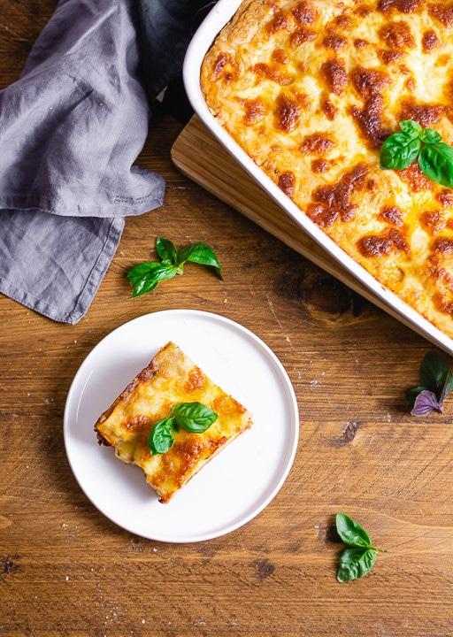 Ein Stück italienische Lasagne mit viel Käse auf einem Teller