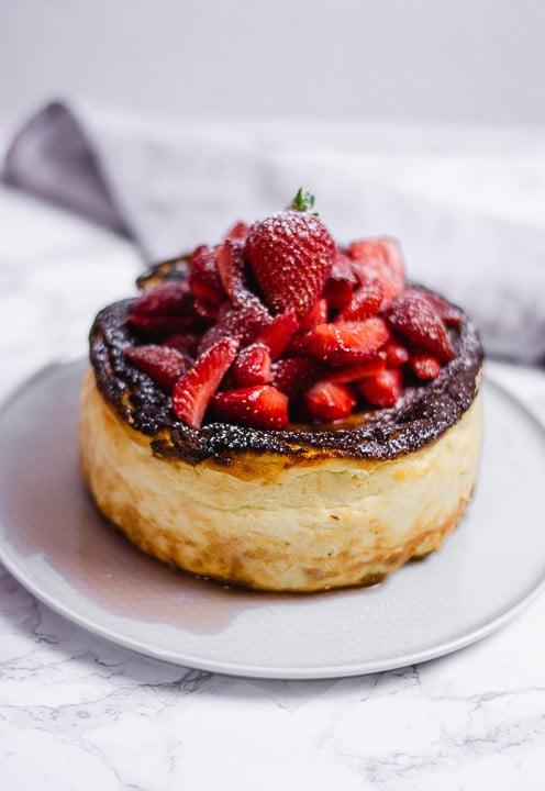 Ein San Sebastian Cheesecake mit ganzen Erdbeeren auf dem Kuchen