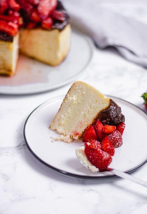 Ein Löffel mit einem Stück San Sebastian Cheesecake mit Erdbeere