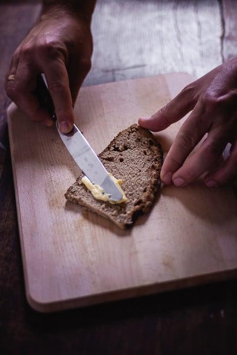 Butter wird auf eine Scheibe Brot geschmiert