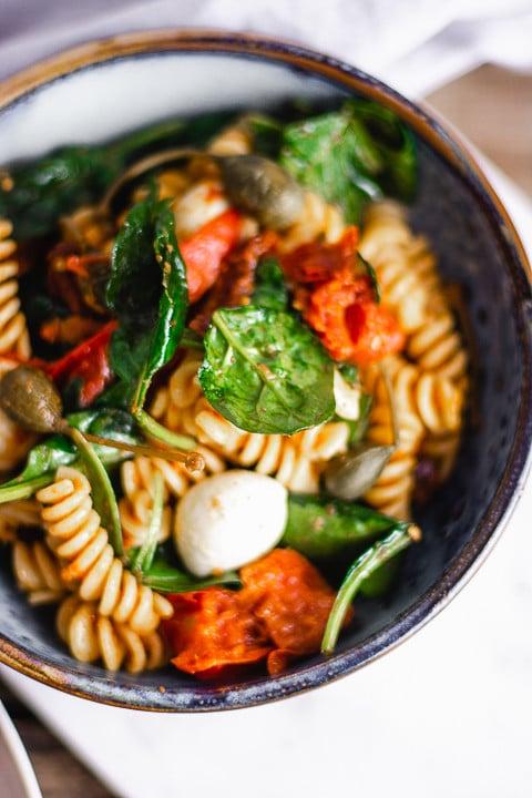 Ein Teller Nudelsalat von oben. Man erkennt Mozzarella, Tomaten, Kapern und Nudeln
