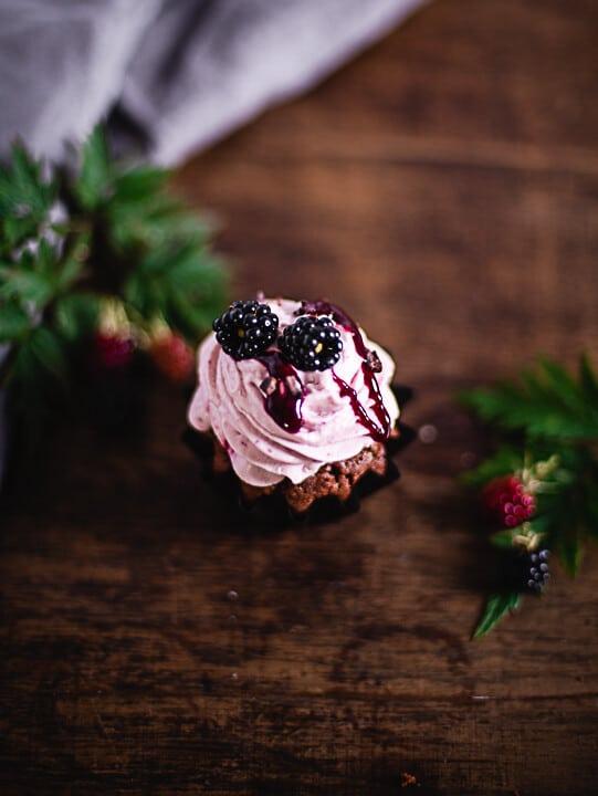 Ein Schoko Brombeer Cupcake mit zwei Bormbeeren und Sauce