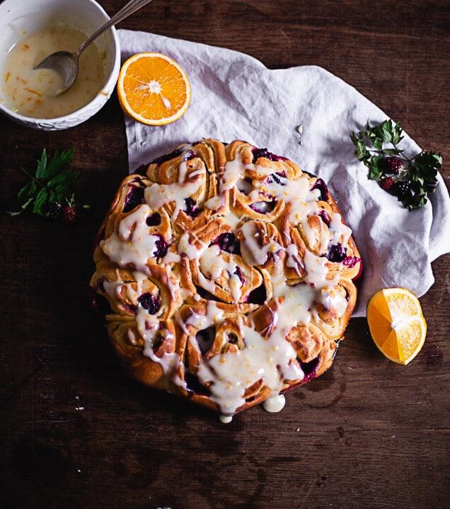 Hefeschnecken auf dunklem Tisch mit Glasur und Orangen