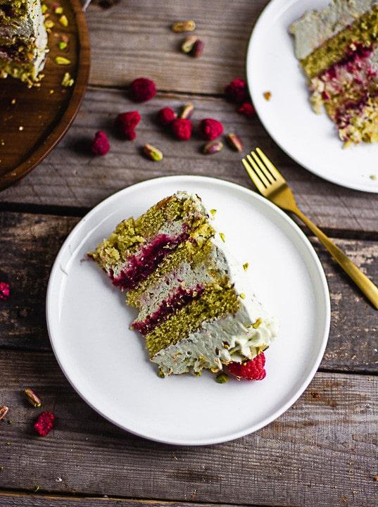 Ein Stück Pistazienkuchen auf einem weißen Teller. Daneben liegt eine goldene Gabel