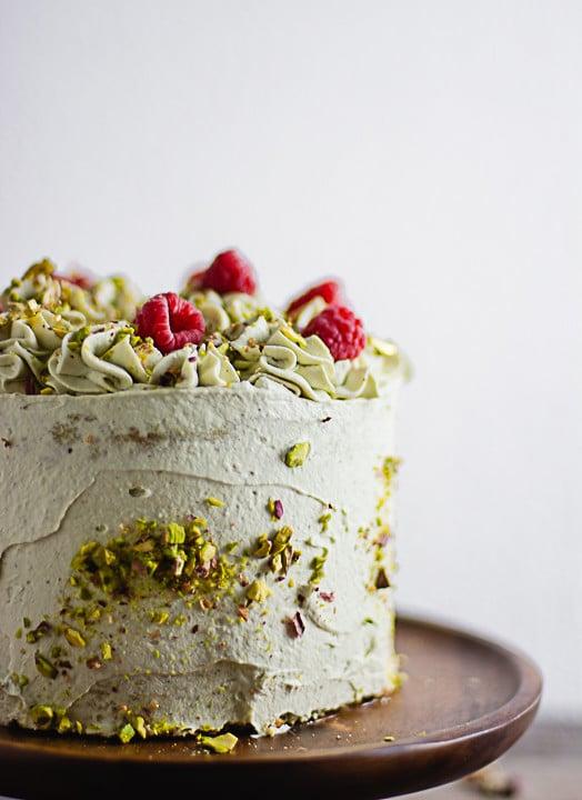 Ein Pistazienkuchen von der Seite. Man erkennt ganz viele Pistazienkerne an der Seite des Kuchens, dekoriert mit Himbeeren