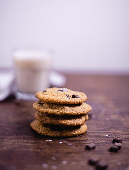 Vier gestapelte Cookies mit weichem Kern. Die Cookies haben Schokoladenstückchen und im Hintergrund sieht man ein Glas Milch