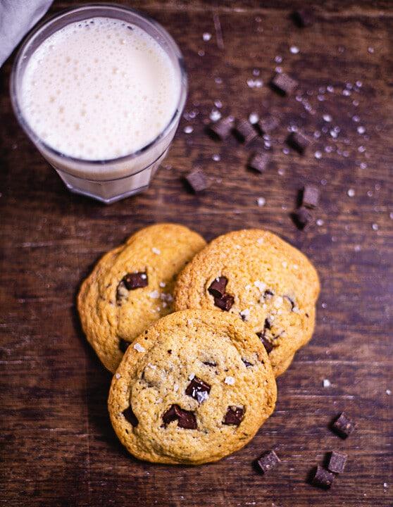 Drei Schokoladen Cookies mit weichem Kern und daneben ist ein Glas Milch
