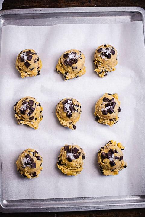 Neun Cookiebällchen auf einem Backblech vor dem backen