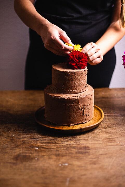Blumen werden an der Geburtstagstorte angebracht