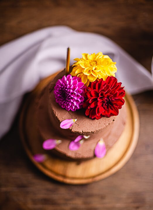 Die Geburtstagstorte von oben. Man erkennt eine Kerze und Blumen