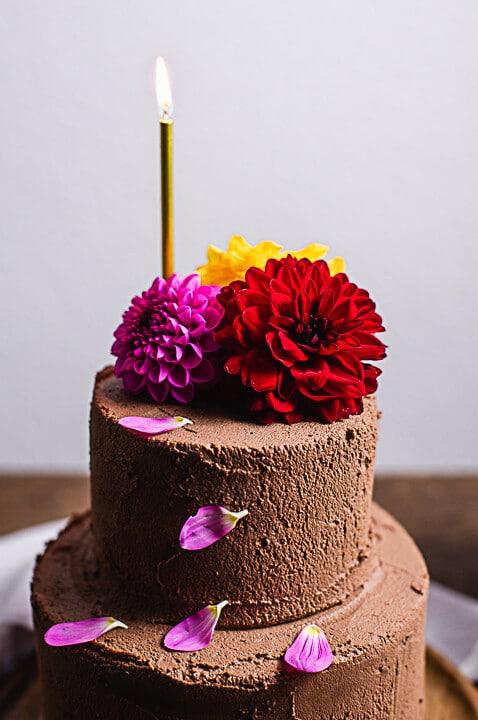 Ein schokoladiges Geburtstagstorten Rezept. Der Kuchen ist dekoriert mit Blumen und einer brennenden Kerze