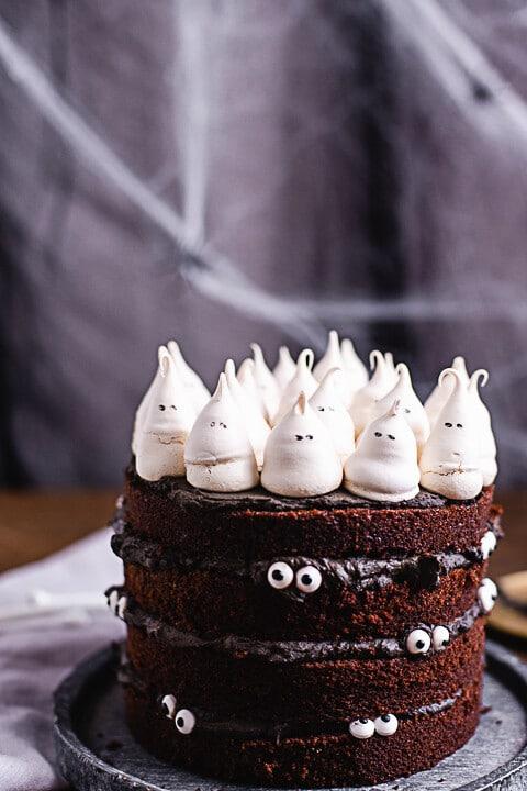 Viele kleinen Gerister auf der Halloween Torte. Im Hintergrund ist es gruselig dekoriert