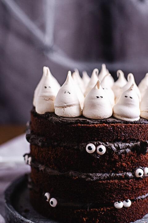 Auf der Halloween Torte sitzen kleine Geister aus Baiser. An der Seite der Torte sind Augen befestigt. Es wirkt als würde Torte einen anschauen