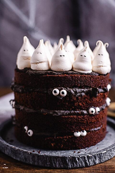 Kleine Baisers dekoriert als Gespenster, sitzen auf der Halloween Torte