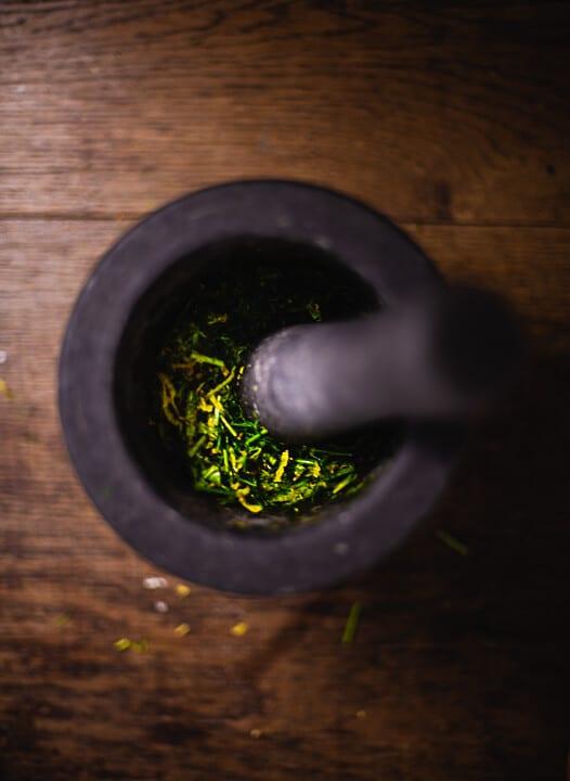 Grünzeug wird in einem Mörser zerkleinert