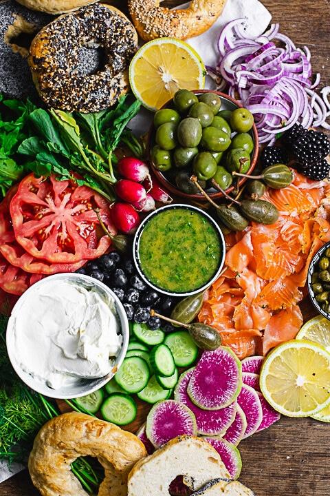 Eine Lachsplatte als Topshot. Man sieht Bagel, Oliven, Zwiebeln, Oliven, Tomaten, Frischkäse und mehr