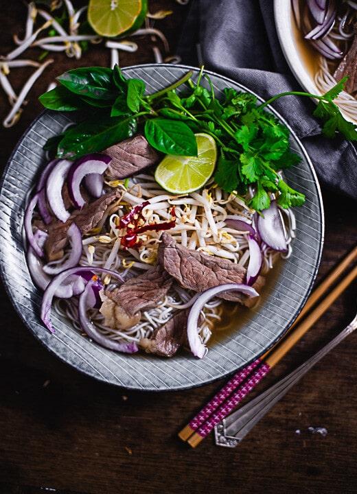 Ein Teller Pho Bo mit Zwiebeln, Fleisch, Soja, und Suppe