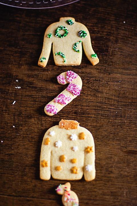Zwei hässliche Weihnachtspullover, eine Zuckerstange und ein Bonbon als Butterplätzchen